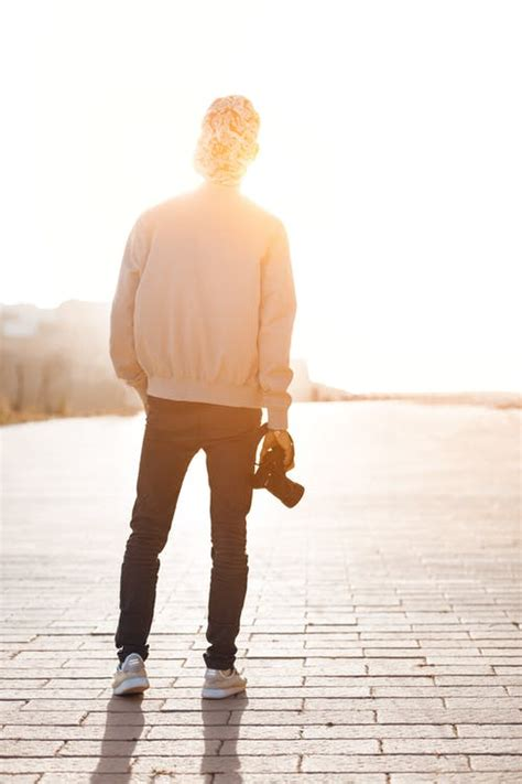 Boy Standing While Holding Camera Overlooking Sunlight at